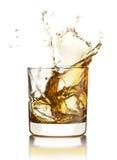 Whisky som plaskar ut ur exponeringsglaset med iskuber  Arkivfoton