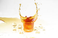 Whisky splash in a transparent glass and ice slices on a white b. Ackground, dynamics of a liquid royalty free stock image