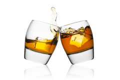Whisky. Splash of whisky in two glasses isolated on white background Royalty Free Stock Photo