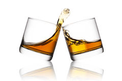 Whisky. Splash of whisky in two glasses  on white background Royalty Free Stock Images