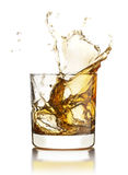 Whisky splashing out of the glass with ice cubes  Stock Photos