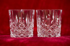Whisky tumbler glasses on red velvet. Two empty whisky tumbler glasses on a red velvet backdrop, ready for an evening's drinking in a high class establishment or Stock Photo