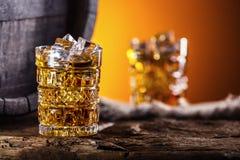 whisky Twee koppen hoogtepunt van de brandewijn of de cognac van de drankwhisky met ijsblokjes in retro stijl Oud eiken vat op de royalty-vrije stock foto's