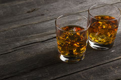 Whisky in two glasses on a dark wooden background Royalty Free Stock Photos