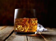 Whisky und Eis in einem transparenten Glas auf einem hölzernen Hintergrund Stockfotografie