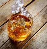 Whisky und Eis in einem transparenten Glas auf einem hölzernen Hintergrund Stockfoto