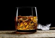 Whisky und Eis in einem transparenten Glas auf einem hölzernen Hintergrund Lizenzfreie Stockbilder