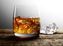 Whisky und Eis in einem transparenten Glas auf einem hölzernen Hintergrund Lizenzfreie Stockfotos