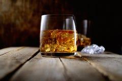 Whisky und Eis in einem transparenten Glas auf einem hölzernen Hintergrund Stockfotos