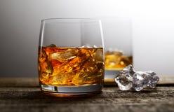 Whisky und Eis in einem transparenten Glas auf einem hölzernen Hintergrund Lizenzfreies Stockbild