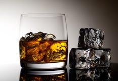 Whisky und Eis in einem transparenten Glas auf einem hellen Hintergrund Stockbild