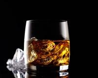 Whisky und Eis in einem transparenten Glas auf einem schwarzen Hintergrund Stockfotografie