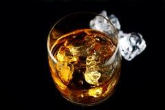 Whisky und icein ein transparentes Glas auf einem schwarzen Hintergrund Lizenzfreies Stockbild