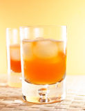 Whisky, whiskey. Two whisky glasses in yellow and orange colourtones royalty free stock images