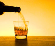 Whisky and Whiskey Being poured. Whiskey being poured with Orange background stock images