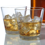 Whisky or Whiskey in a glass and bottle with ice cubes Stock Image