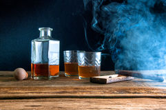 Whisky y cigarro en la tabla de madera Foto de archivo