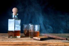 Whisky y cigarro en la tabla de madera Fotografía de archivo