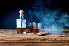 Whisky y cigarro en la tabla de madera Fotos de archivo
