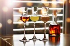 Whisky y licor delante de una ventana Imagenes de archivo
