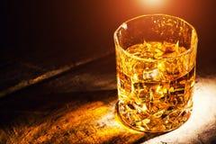 Whisky z kostka lodu na drewnianym tle zdjęcia stock