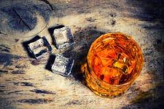 Whisky z kostka lodu na drewnianym tle obrazy stock
