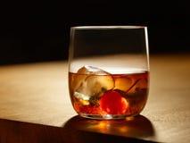 Whiskycoctailen på vaggar med en körsbär royaltyfria foton