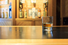 Whiskyexponeringsglas i en stång Royaltyfri Foto