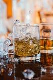 Whiskyexponeringsglas med is och varmt ljus på den svarta tabellen med reflexionen, varm atmosfär Arkivfoton