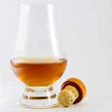 Whiskyexponeringsglas med whisky och en kork Royaltyfri Foto
