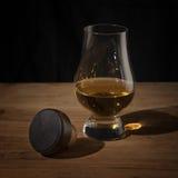 Whiskyexponeringsglas och kork på trätabellen Royaltyfri Foto