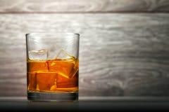Whiskyexponeringsglas och is på träbakgrund fotografering för bildbyråer
