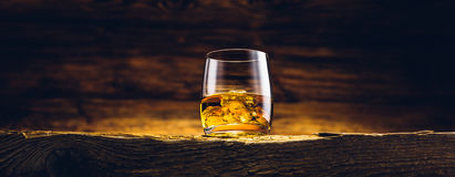 Whiskyexponeringsglas på den gamla tabellen Arkivbild