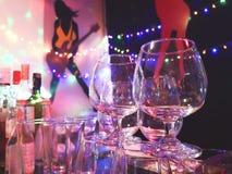 Whiskyexponeringsglas på ett parti på natten arkivbild
