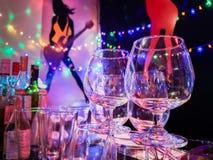 Whiskyexponeringsglas på ett parti på natten royaltyfria foton