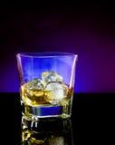 Whiskyexponeringsglas på ljust tonvioletdisko Royaltyfri Fotografi