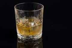Whiskyexponeringsglas på svart glass yttersida med reflexioner Royaltyfria Bilder