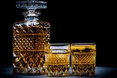 Whiskyflasche und -gläser mit schwarzem Hintergrund lizenzfreie stockfotografie