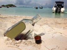 Whiskyflaska på stranden Royaltyfria Foton