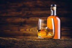 Whiskyglas en fles op de oude lijst stock afbeelding