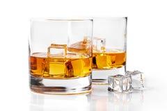 Whiskyglazen met ijsblokjes op wit worden geïsoleerd dat Stock Foto's
