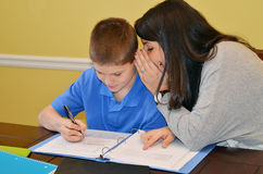 Whisper. Tutor giving her student a clue in a whisper Stock Images