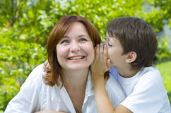 Whisper. Portrait of a young boy with his mother in summer environment Royalty Free Stock Image