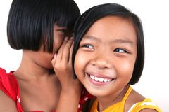 Whisper. Two young asian kids whispering Royalty Free Stock Image