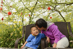 Whisper. Chinese mom whisper with son , trees background stock photos