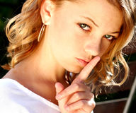 Whisper please. Female model finger to mouth Stock Photography