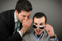 Whisper Words. Image of a men wearing a suit whispering to another men wearing a suit Royalty Free Stock Photos