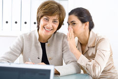 Whispering businesswomen Royalty Free Stock Photos