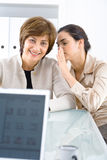 Whispering businesswomen Stock Photo