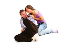 Whispering couple on white. A young couple sitting on the floor, the girl is whispering something to her partner Stock Photos
